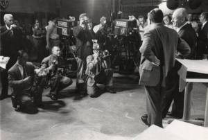 Linus Pauling and Edward Teller with members of the media and television crew during the debate.