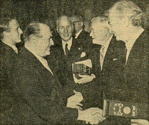 Pauling, holding the case containing his Nobel diploma, being congratulated by Norwegian King Olav V. Image originally published in Morgenbladet, December 11, 1963.